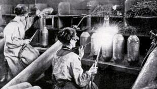 En avril 1916, des femmes soudent des pièces d'obus dans une usine d'armement française.