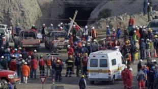 Compañeros y familiares de los mineros aislados montan guardia en el exterior de la boca de la mina.
