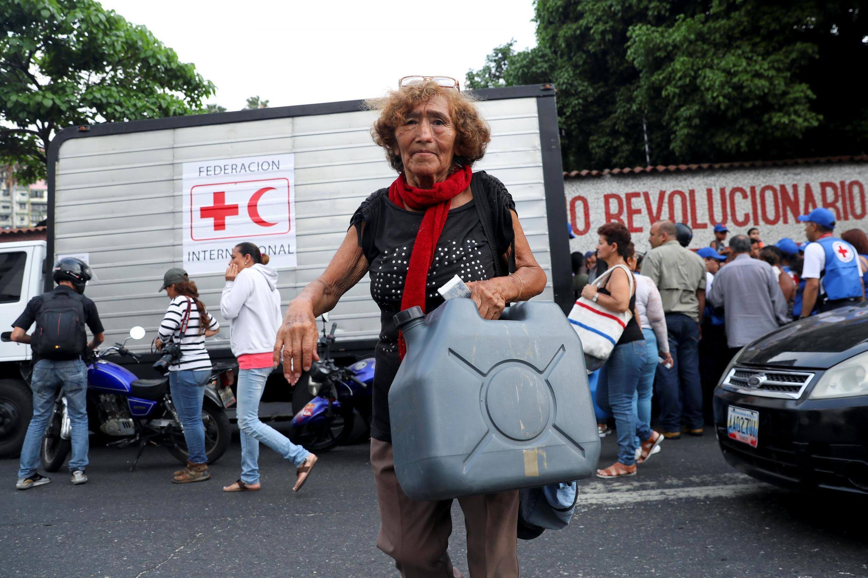 Mulher carrega um recipiente de água e pílulas de purificação de água distribuídas pela Cruz Vermelha venezuelana como ajuda humanitária no bairro Água Salud em Caracas, Venezuela, 16 de abril de 2019.