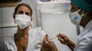 Une soignante reçoit une dose du vaccin cubain anti-Covid-19, Soberana 2, dans le cadre des essais de phase 3, à la Havane, le 24 mars 2021.