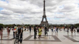 Des policiers à vélo portant des masques faciaux patrouillent sur l'esplanade du Trocadéro, près de la tour Eiffel, le 24 août 2020, à Paris.
