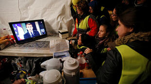 French Yellow Vest protesters watch the speech of President Emmanuel Macron at the town of La Ciotat, near Marseille, 10 December 2018.