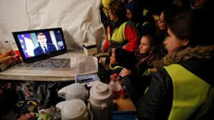 """""""Coletes amarelos"""" assistindo à intervenção televisiva de segunda-feira em que o Presidente Macron prometeu nomeadamente um aumento de 100 Euros do ordenado mímino."""