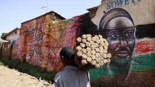 A hawker carries brooms for sale as he walks past a mural promoting peace in Kibera slum