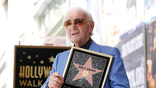 The singer Charles Aznavour posing with his star, in Los Angeles, 24 August 2017