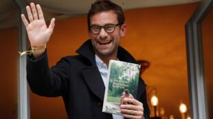 """Nicolas Mathieu com seu livro """"Leurs enfants après eux"""" na mão"""