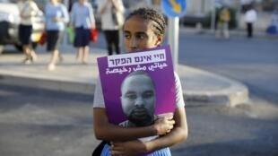 Une jeune fille israélienne tient une affiche de Solomon Tekah, un jeune homme d'origine éthiopienne qui a été tué par un officier de police en dehors de ses fonctions.