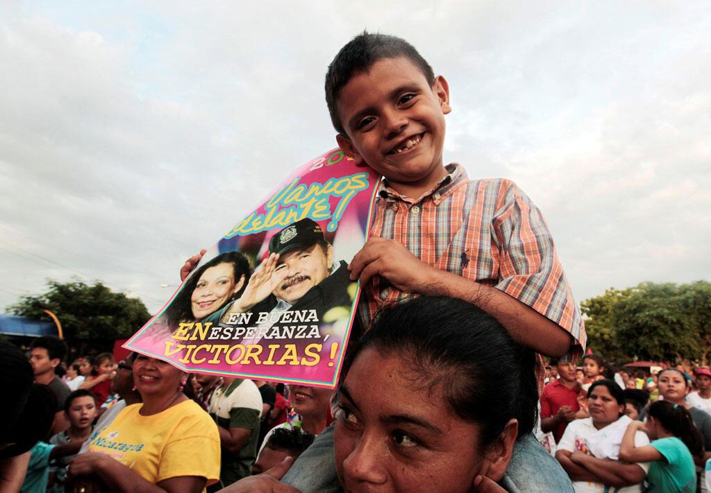 Un garçon tient une affiche de campagne du président Daniel Ortega et de la première dame et candidate à la vice-présidence, Rosario Murillo lors d'un meeting de campagne de clôture à Cuidad Sandino, au Nicaragua le 23 octobre 2016.