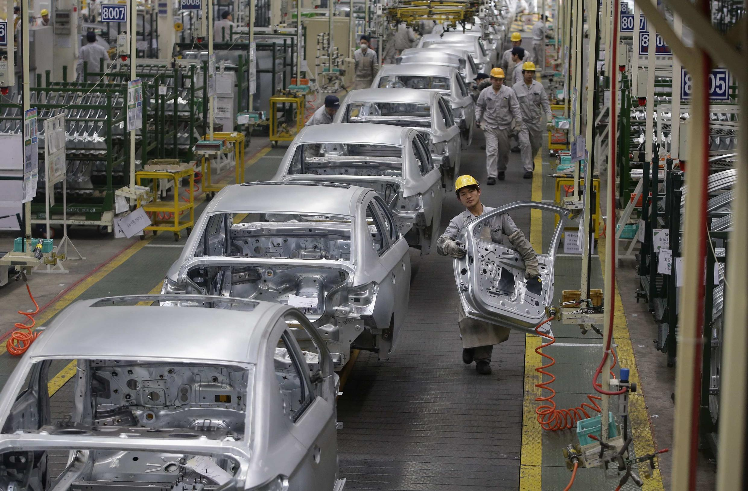 An employee holds a car door at a production line of a Peugeot Citroen Automobile factory in China.