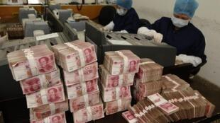 Empleados cuentan billetes en un banco chino en Changzhi, 24 de febrero de 2010.