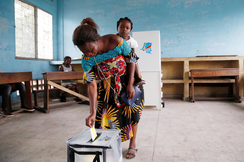 Une femme dépose son bulletin dans l'urne dans un bureau de vote de Kinshasa le 30 décembre 2018.