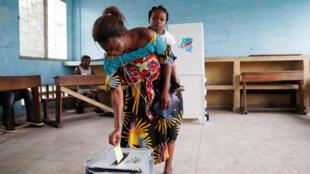Une femme dépose son bulletin dans l'urne dans un bureau de vote de Kinshasa le 30 décembre 2018 (image d'illustration).