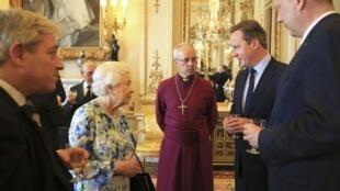 Le reine Elizabeth II discute avec le Premier ministre David Cameron lors d'une réception à Buckingham Palace à Londres, le 10 mai 2016.