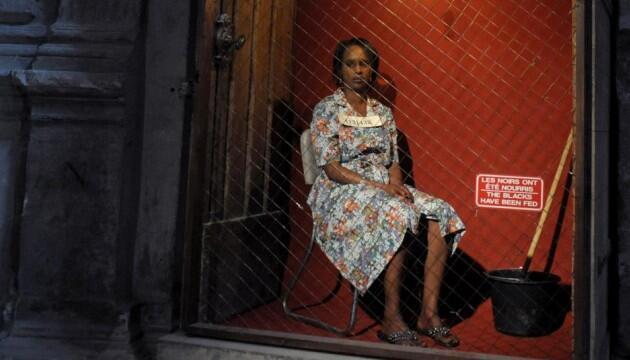 """Cena de """"Exhibit B"""" mostra mulher negra enjaulada, no espaço cultural Centquatre, em Paris"""