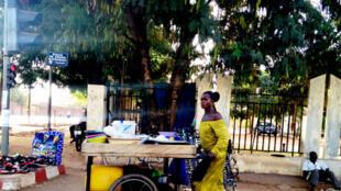 Une commerçante ambulante pousse son comptoir mobile sur l'avenue Kwame NKrumah de Ouagadougou au Burkina-Faso