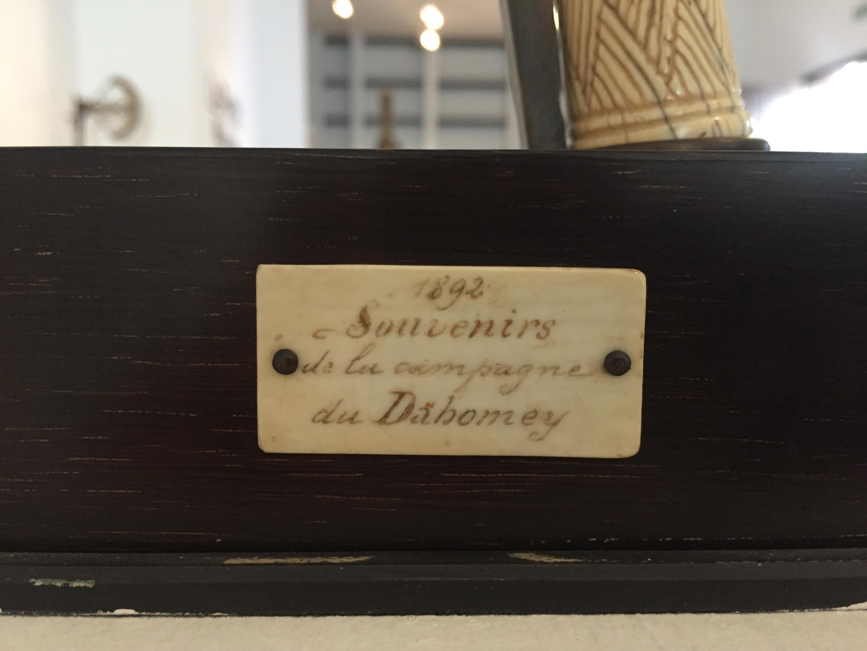 Cette plaque fixée sur le panneau de présentation d'une récade du roi Glélé indique qu'elle aurait été prise lors de la conquête du royaume du Dahomey par les Français.