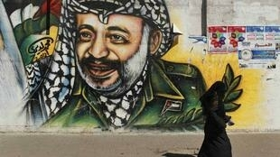 A Palestinian woman walks past a mural depicting late leader Yasser Arafat in Gaza City