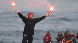 French skipper Francois Gabart celebrates with safety flares as he sails the trimaran Macif into Brest harbour