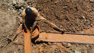 Un homme travaille dans une mine d'or à ciel ouvert en République démocratique du Congo.