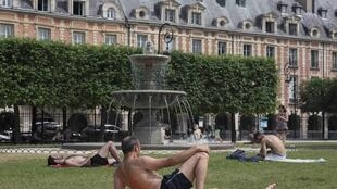 Sunbathers in Place des Vosges, central Paris on 3 July 2015