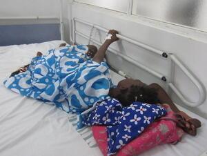 Lors d'une pénurie de morphine au Sénégal, une patiente souffrant d'un cancer s'agrippe à la barre d'appui de de son lit d'hôpital à Dakar, le médicament requis étant indisponible.