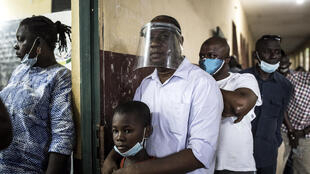 Guineanos hacen fila en un colegio electoral de Conakry para elegir nuevo presidente, el 18 de octubre de 2020