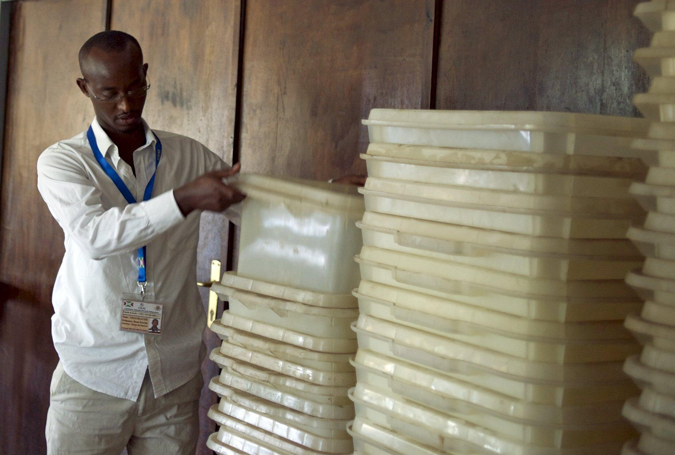 A member of Burundi's National Electoral Commission counts ballot boxes at a warehouse used to store electoral material for the upcoming parliamentary elections, in the neighbourhood of Nyakabiga near the capital Bujumbura, 28 June 2015.