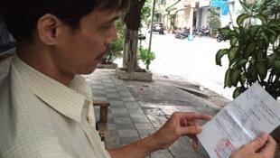 Nhà báo Phạm Chí Dũng và giấy triệu tập của công an. Ảnh chụp ngày 03/03/2015