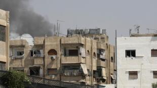 Fumée au-dessus des immeubles du quartier de Midan, à Damas. Photo prise sous le contrôle du gouvernement syrien, le 20 juillet 2012.