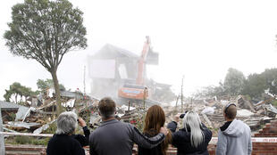 A family watches as their earthquake-damaged home in Christchurch is demolished, 26 February 2011