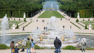 Visitors look at the Latona fountain at the Chateau de Versailles.