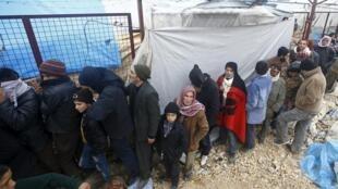 Người tị nạn Syria xếp hàng nhận hàng cứu trợ.