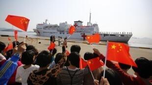 Des proches de l'équipage du navire hôpital l'«Arche de la paix» saluent le départ du bateau dans l'île de Zhoushan, le 21 novembre 2013.