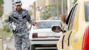 Un policier irakien inspecte des véhicules à un check-point dans Bagdad le 3 mai 2011.