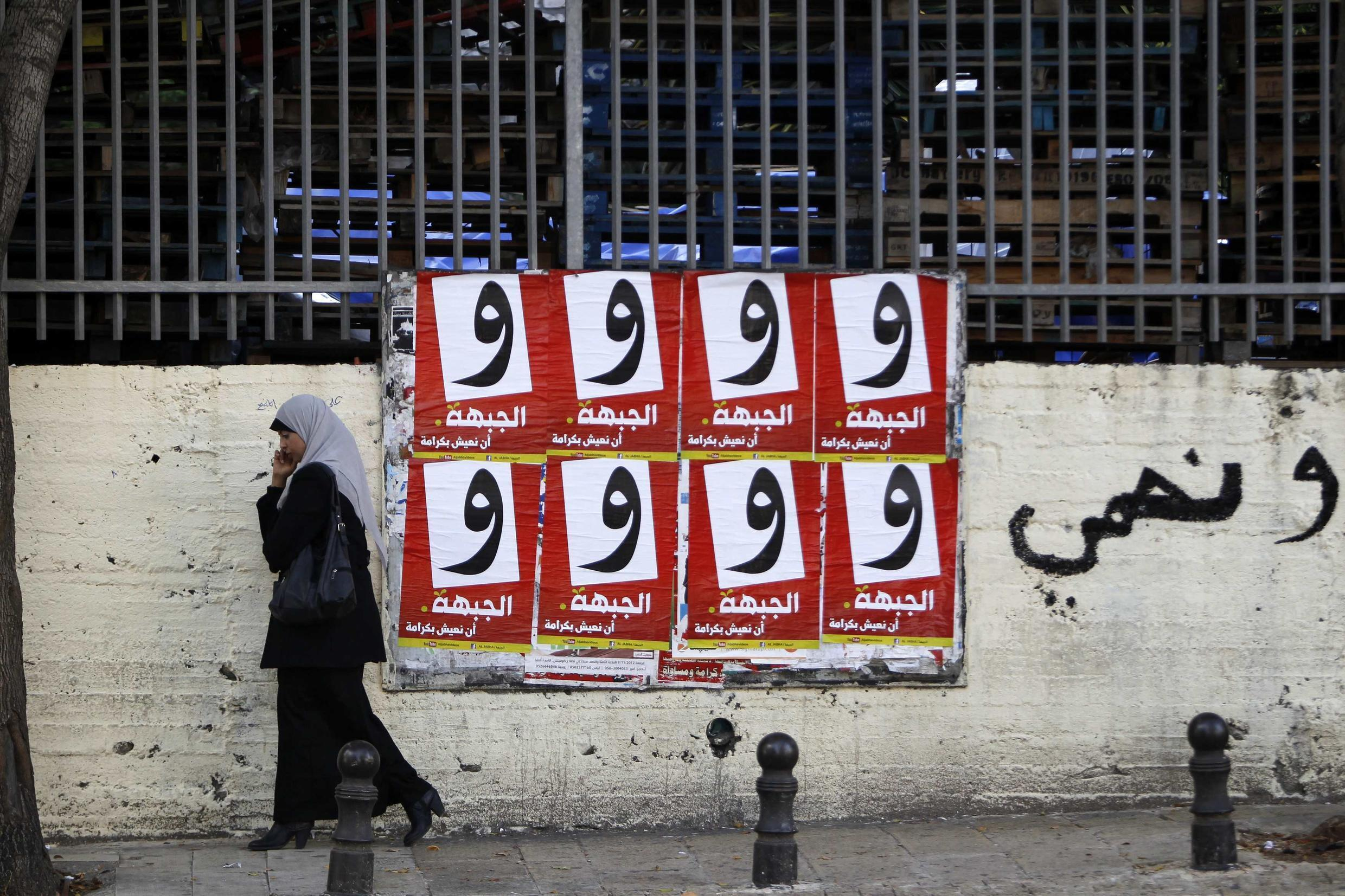 A woman walks past campaign posters for the Arab-led Hadash party