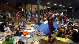 Asylum-seekers wait outside a train station in Budapest.