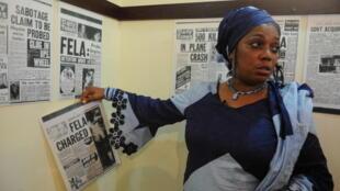 Yeni Kuti, fille de Fela et soeur de Femi et Seun, en 2012, au Kalakuta Republic Museum de Lagos, le musée en l'honneur de son père, montre une couverture de journal titrant « Fela inculpé ».