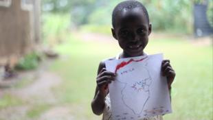 WAni yaro dauke da takarda mai zanen taswirar Afrika