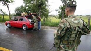Soldados colombianos fazem busca em veículos na área rural de La Montanita, região onde o jornalista francês Romeo Langlios foi sequestrado pelas FARC.