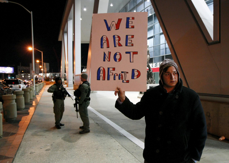 Policiais americanos patrulham em Atlanta na Geórgia próximo ao estádio Philips. Passante mostra um cartaz: nós não temos medo.