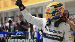 Lewis Hamilton acena para a multidão após conseguir a pole position do GP da Hungria, que acontece no domingo.