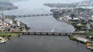 Vue aérienne d'Abidjan et du pont Félix-Houphouët-Boigny au premier plan.