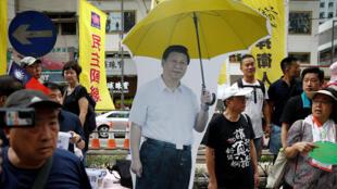 Les manifestants du défilé du 1er juillet autour de l'effigie de Xi Jingping. Le parapluie jaune symbolisant «l'ocupation chinoise».