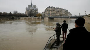 Two men fish on the flooded banks of the River Seine in Paris.