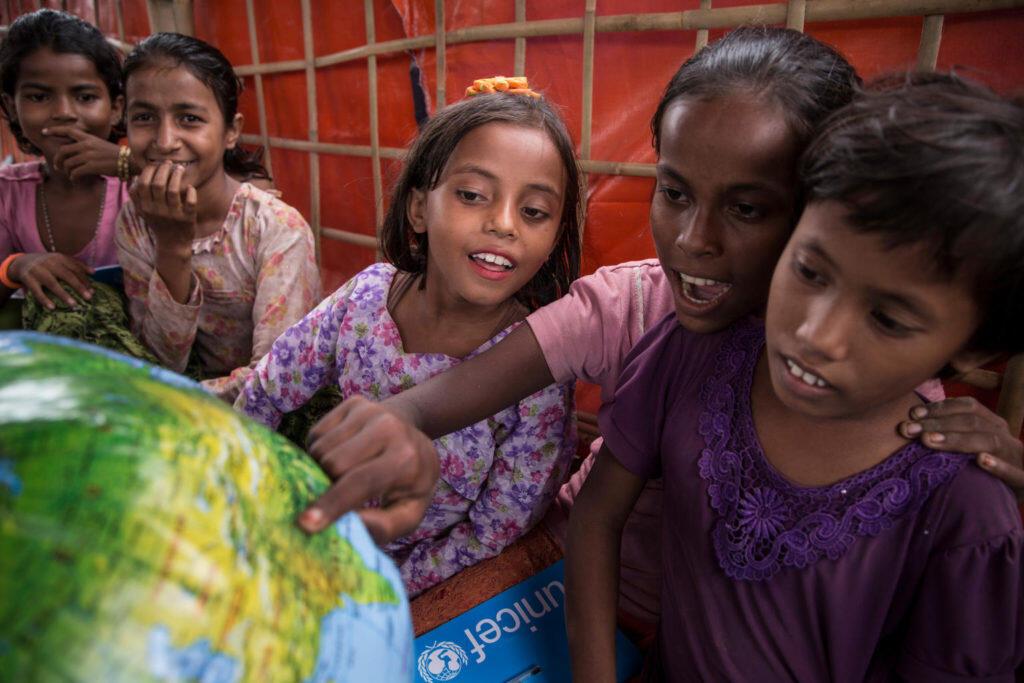 """Um grupo de meninas de um centro de aprendizado temporário no campo de refugiados em Uchiprang, perto de Cox's Bazar, em Bangladesh, estuda com um balão inflável que faz parte da """"escola em uma caixa"""" de materiais educativos distribuídos pela UNICEF."""