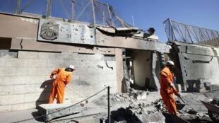 2014年11月13日,阿拉伯聯合酋長國駐的黎波里使館附近發生爆炸。圖為清潔工人在清理爆炸現場。