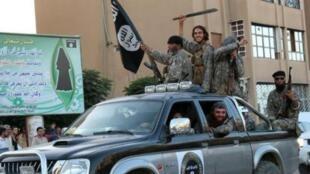 Picha ya propaganda iliyotolewa na vyombo vy habari vya  kijihadi vya Welayat Raqa,  inaonyesha wapiganaji wa kundi la Islamic State wakifanya maonyesho ya kijeshi katika mji wa Raqa, Juni 30, 2015, Syria.