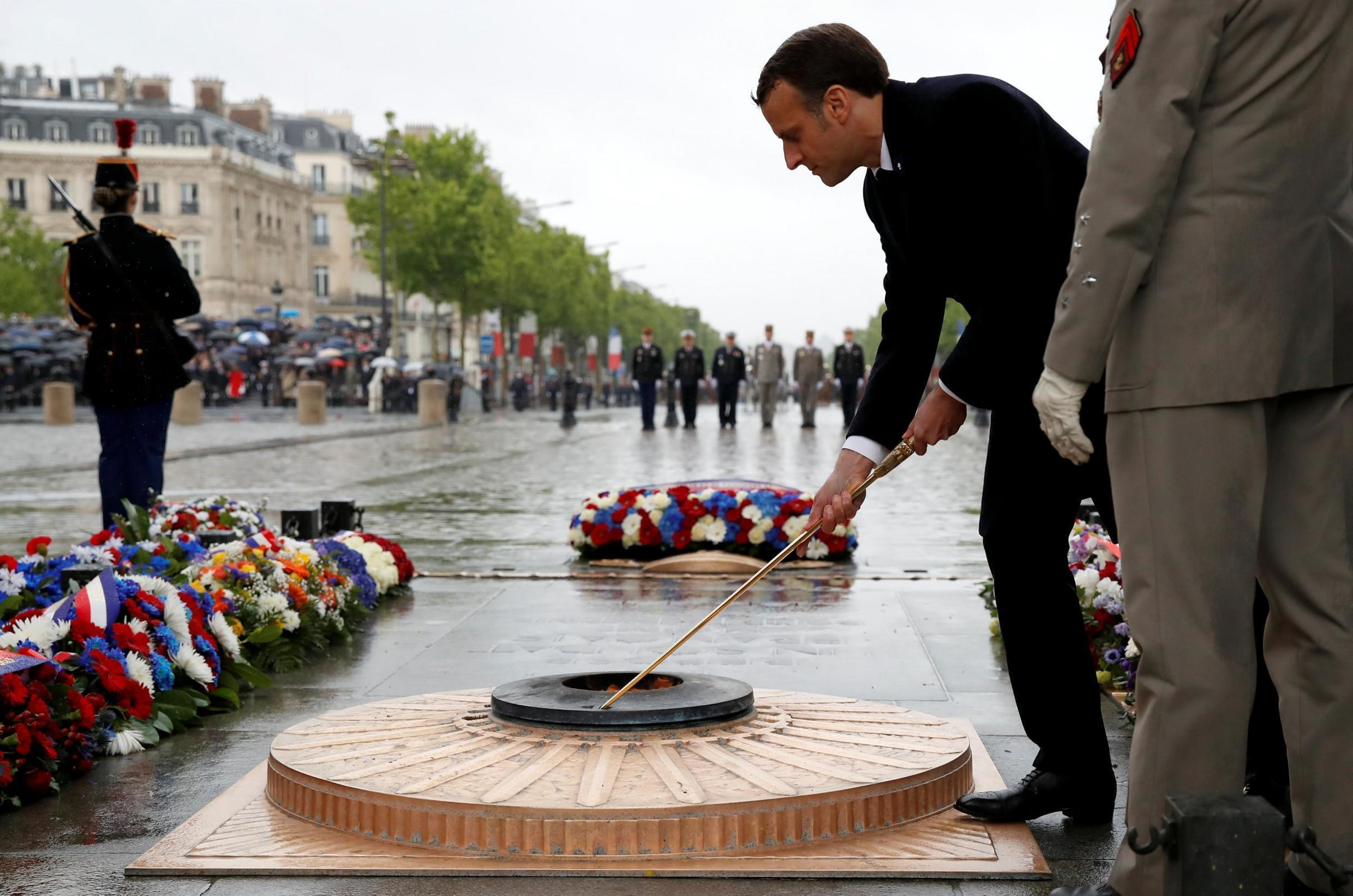 French President Emmanuel Macron lights the fire at the tomb of the Unknown Soldier during a ceremony commemorating the end of World War Two in Paris, 8 May 2019.