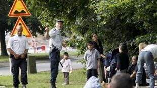 Police evacuate a Roma family near a traffic circle in Villeneuve-d'Ascq after their caravan was removed from an illegal camp