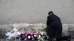 A man pays his respects under a commemorative plaque unveiled by French President François Hollande during a ceremony held for the victims of last year's Paris attacks.